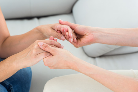 psychologist: Therapist holding her patients hands on white background