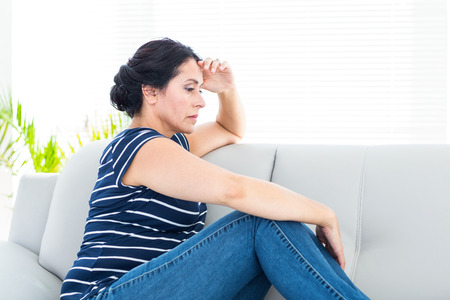 wistfulness: Unhappy woman sitting on the couch on white background Stock Photo