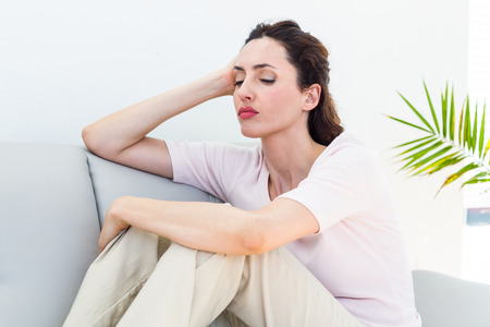 desolaci�n: Sad brunette sitting on the couch on white background