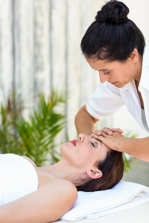 woman in towel: Brunette receiving forehead massage at the spa Stock Photo