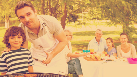 extended family: Father and son at barbecue grill with extended family having lunch in the park Stock Photo