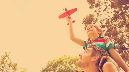 and shoulders: Ángulo de visión baja de un niño con avión de juguete que se sienta en hombros de padres en el parque