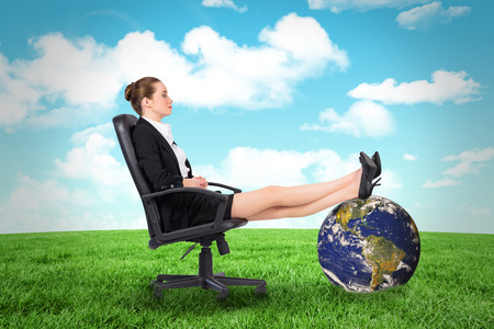 swivel: Businesswoman sitting on swivel chair with feet up against field and sky