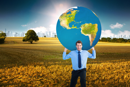 mid distance: Businessman carrying the world against field with tree and city on the horizon