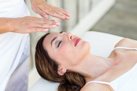 40335934: Calm woman receiving reiki treatment in the health spa Stock Photo