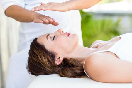 treatment: Calm woman receiving reiki treatment in the health spa Stock Photo
