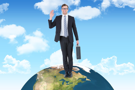 businessman carrying a globe: Geeky hipster businessman waving at camera  against blue sky