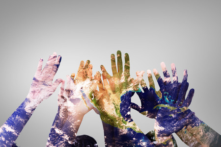 raising hands: People raising hands in the air against grey vignette Stock Photo