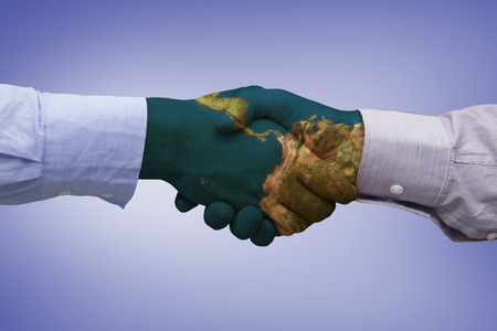 international business agreement: Hand shake in front of wires against purple vignette Stock Photo