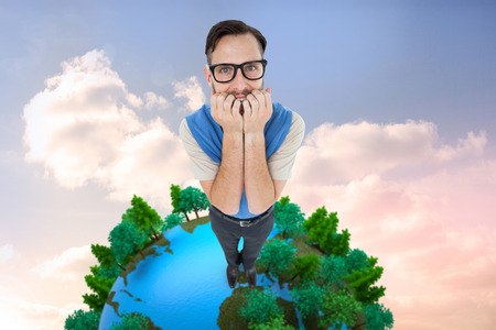 Geeky hipster looking nervously at camera against beautiful blue cloudy sky photo