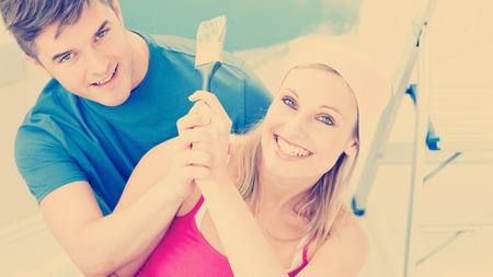 Hugging couple having fun while painting a room in their new house