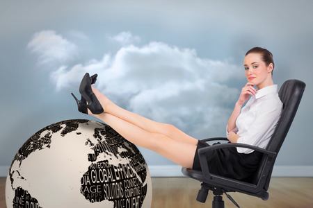 Businesswoman sitting on swivel chair with feet up against clouds in a room photo