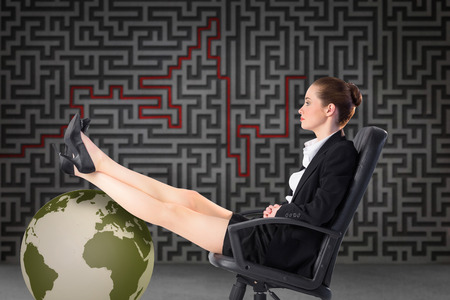 Businesswoman sitting on swivel chair with feet up against grey maze photo