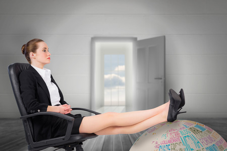 swivel: Businesswoman sitting on swivel chair with feet up against open door leading to bright window Stock Photo