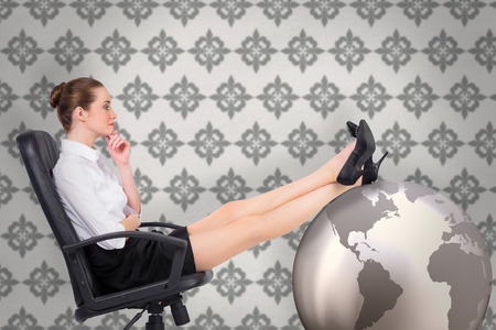 swivel: Businesswoman sitting on swivel chair with feet up against grey wallpaper Stock Photo