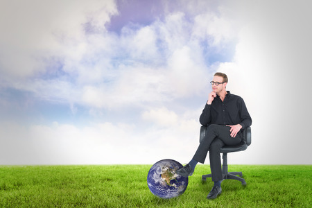 swivel: Thoughtful businessman sitting on a swivel chair against green field