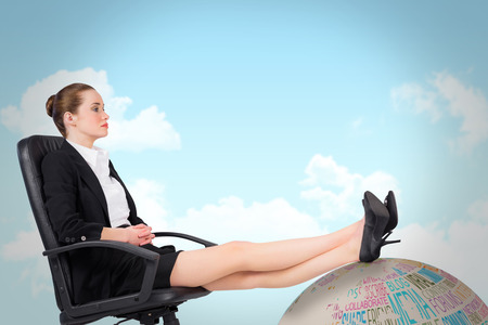 swivel: Businesswoman sitting on swivel chair with feet up against blue sky