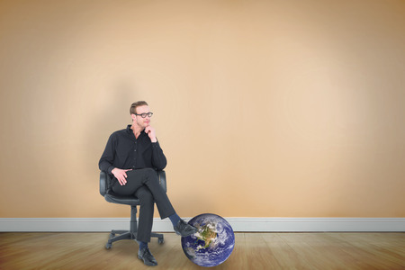 swivel: Thoughtful businessman sitting on a swivel chair against room with wooden floor