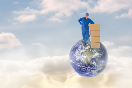 boiler suit: Happy delivery man leaning on pile of cardboard boxes against beautiful blue sky with clouds