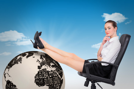 swivel chair: Businesswoman sitting on swivel chair with feet up against blue sky