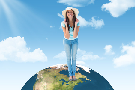 sunhat: Happy young brunette wearing sunhat against blue sky Stock Photo