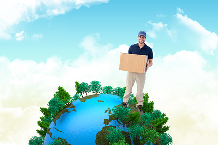 tree world tree service: Happy delivery man holding cardboard box against blue sky