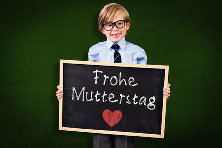 pupil: Cute pupil holding chalkboard against green Stock Photo