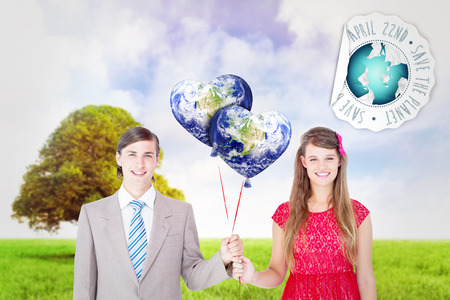 Smiling geeky couple holding red balloons against tree in green field photo