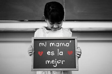 schoolchild: Spanish mothers day message against schoolchild with blackboard Stock Photo