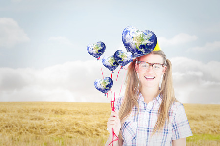 cheesy grin: Geeky hipster smiling at camera and holding red balloons  against bright brown landscape Stock Photo