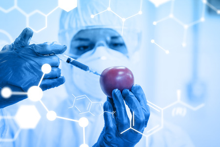 Science graphic against researcher in protective suit injecting tomato at lab photo