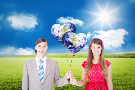 together with long tie: Smiling geeky couple holding red balloons against sunny green landscape
