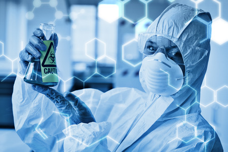 Science graphic against scientist in protective suit with hazardous chemical in flask Stock Photo