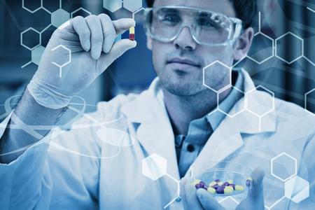 Science graphic against male scientist analyzing pills in the laboratory