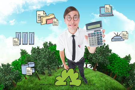 Geeky smiling businessman showing calculator  against blue sky photo