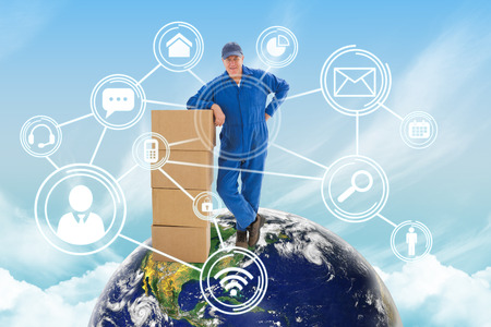 boiler suit: Happy delivery man leaning on pile of cardboard boxes against blue sky