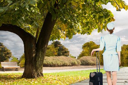 hotesse de l air: Jolie h�tesse de l'air se penchant sur valise contre d�cor pittoresque Banque d'images