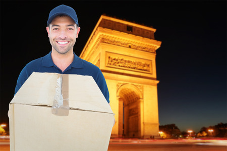 triumphe: Happy delivery man holding cardboard box against arc de triumphe in france
