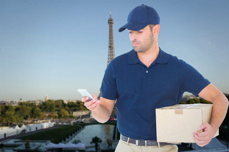 Delivery man using mobile phone while holding package against eiffel tower photo