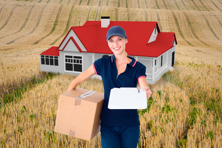 Happy delivery woman holding cardboard box and clipboard against rural fields photo