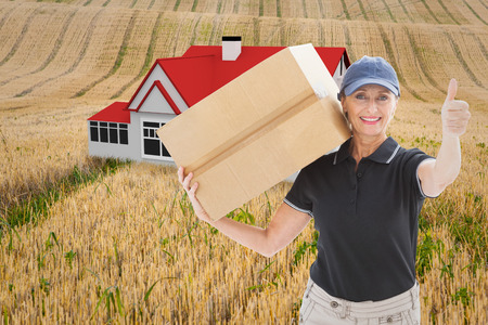 Happy delivery woman holding cardboard box against rural fields photo