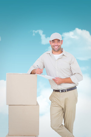 legs crossed on knee: Delivery man with clipboard leaning on cardboard boxes against blue sky