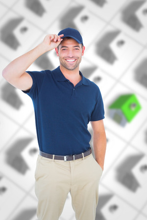 roofed house: Portrait of happy delivery man wearing cap against one green roofed 3d house surrounded by many Stock Photo