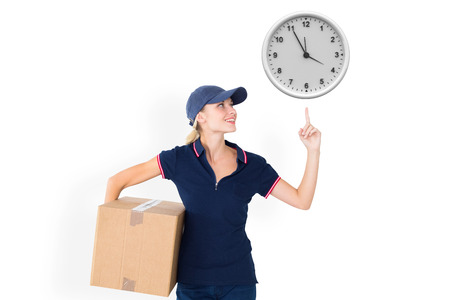 against the clock: Happy delivery woman holding cardboard box and pointing up against clock