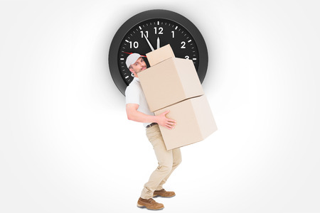 against the clock: Tired delivery man carrying stack boxes  against clock Stock Photo