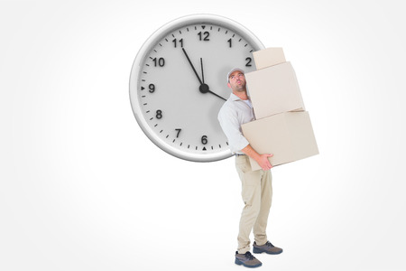 against the clock: Tired delivery man carrying stack boxes against clock