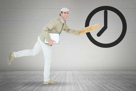 delivery room: Happy delivery man running while holding parcel against grey room Stock Photo