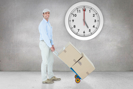 delivery room: Confident delivery man pushing trolley of cardboard boxes against grey room
