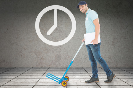 delivery room: Confident delivery man pushing empty trolley against grey room