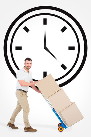 against the clock: Delivery man pushing trolley of boxes against clock Stock Photo